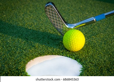 Close up image of golf hole with ball and putt