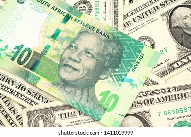 A close up image of a green ten rand bank note from South Africa in macro on a bed of American one dollar bills