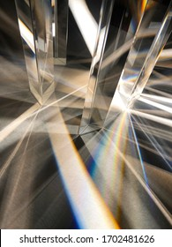 Close up image of group of crystal clear triangular glass prisms refracting and dispersing narrow beam of artificial light into spectrum and cross line pattern on texture paper. Triangular pattern