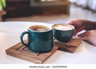 Close up image of a hand holding a green coffee mugs in cafe
