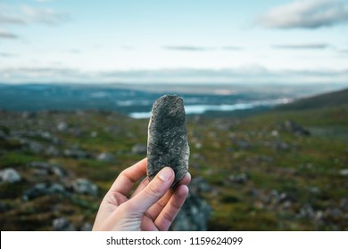 Close up image of hand holding rock on a background of blue sky with clouds and green landscape