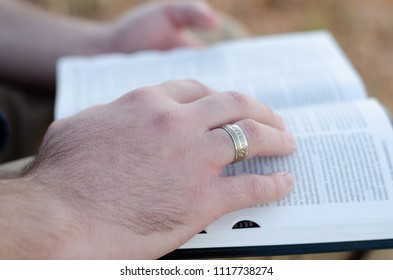 A close up image of the hand of a man reading his bible in the outdoors with the focus on a ring he is wearing on his right hand ring finger.