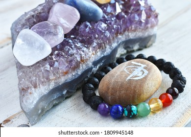 A close up image of a handmade chakra bracelet and amethyst geode on a wooden table top.