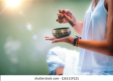 Close up image of woman's hands holding Tibetan bowl by the Water