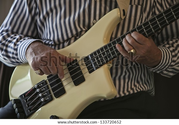 Close up image of hands of a mature man strumming on an electric bass guitar.