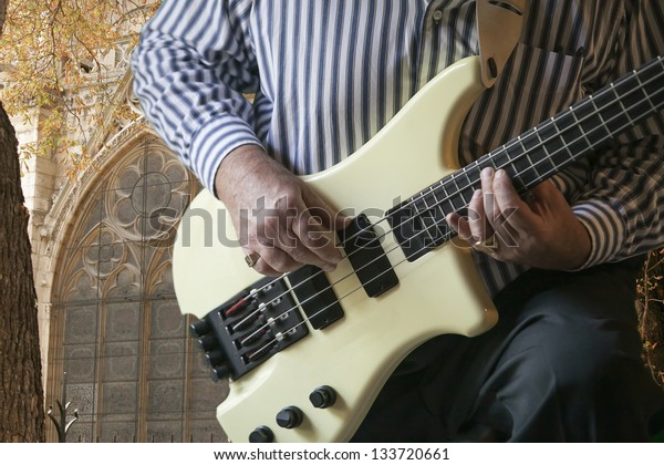 Close up image of hands of a mature man strumming on an electric bass guitar. Church window is in background.