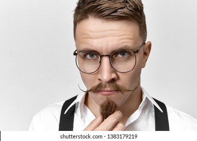 Close up image of handsome charming European man with blue eye and stylish mustache stroking his goatee beard, thinking over something important, having focused concentrated facial expression