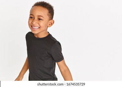 Close up image of handsome emotional dark skinned little boy with short Afro hair wearing black t-shirt having fun, laughing out loud, opening mouth widely, showing his white straight teeth