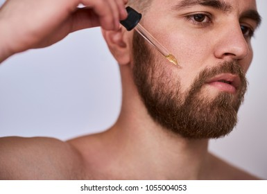 close up image of handsome man with pipette with beard oil