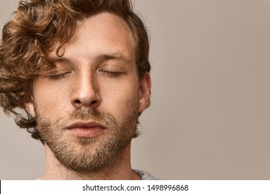 Close up image of handsome young man with stubble and wavy reddish hair keeping eyes closed, having calm peaceful look, meditating against blank studio wall background with copyspace for your text