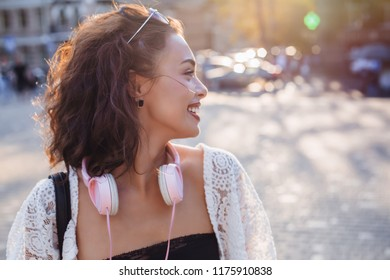Close up image of happy brunette woman in sunglasses and autumn clothes posing sideways outdoors.Happy woman in sunglasses,headphones and dress walking outdoors.