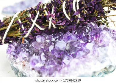 A close up image of a healing smudge stick with lilac flowers and amethyst crystal.
