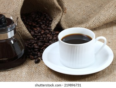 close up image of hot black coffee and coffee beans