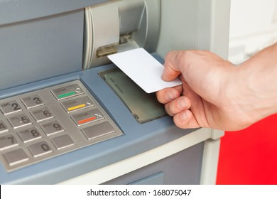Close up image of a human hand inserting a credit card in the ATM