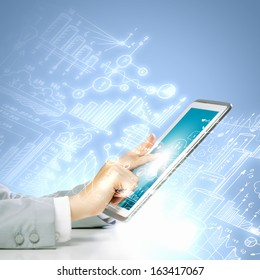 Close up image of human hand touching screen of tablet pc