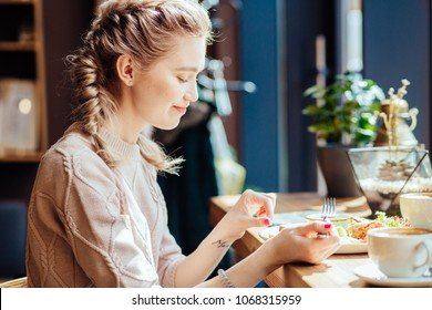 Close up image of hungry blond woman eating classic breakfast a tasty omelet, fresh salad and toasts, coffee in modern loft cafe interior. This energy boost for the whole day.