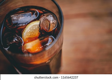 Close up image of Ice cold carbonated or fizzy beverage with lemon slice on wooden table