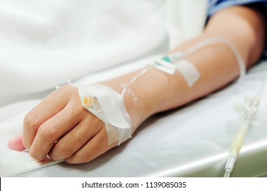Close up image of IV drip in patient's hand in hospital.