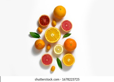Close up image of juicy organic whole and halved assorted citrus fruits, green leaves & visible core texture, isolated white background, copy space. Vitamin C loaded food concept. Top view, flat lay.