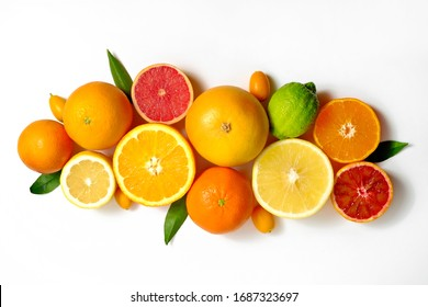 Close up image of juicy organic whole and halved assorted citrus fruits, green leaves & visible core texture, isolated white background, copy space. Vitamin C loaded food concept. Top view, flat lay. - Shutterstock ID 1687323697
