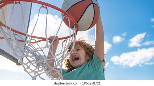 Close up image of kid basketball player making slam dunk during basketball game in floodlight basketball court. The child player is wearing sport clothes.