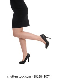 A close up image of the legs and butt of a young woman in a blackdress and high heels, isolated for white background
