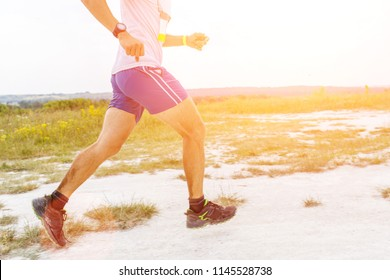 Close up image of legs of man running on sandy ground