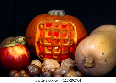 Close up image of a lit, carved Halloween pumpkin of the Celtic Samhain symbol with autumn/fall/harvest fruit, nuts and vegetables against a black background.