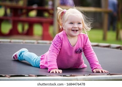Close up image of a little blond toddler girl playing outside