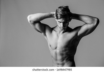 Close up image of a male fitness model flexing his body in a studio