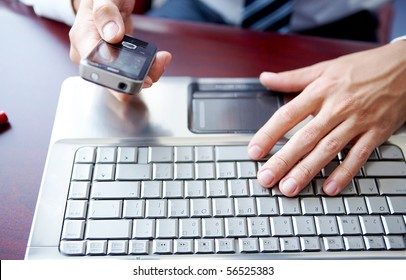Close up image of male hands working on laptop and cell phone