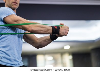 Close up image of man doing side-to-side chops exercise with elastic band at the gym.