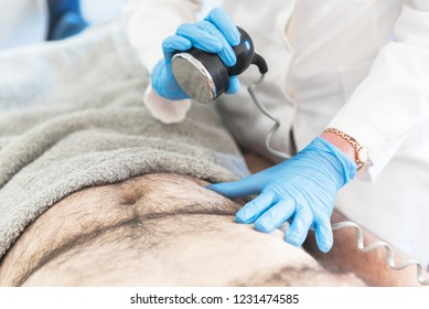 Close up image of man on cavitation, ultrasound, lipolysis body treatment.