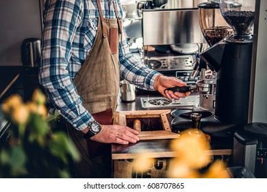 Close up image of a man preparing cappuccino in a coffee machine.