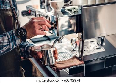 Close up image of a man preparing cappuccino in a coffee machine.