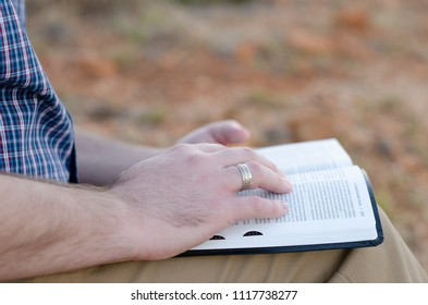 A close up image of a man reading his bible in the outdoors with the focus on a ring he is wearing on his right hand ring finger.