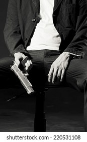 Close up image of A Man sitting on chair holding a Gun