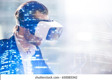 Close up image of man in virtual reality glasses. Guy wearing VR headset working in digital simulation, entertains in cyberspace. Looking on augmented reality double exposure concept with copy space