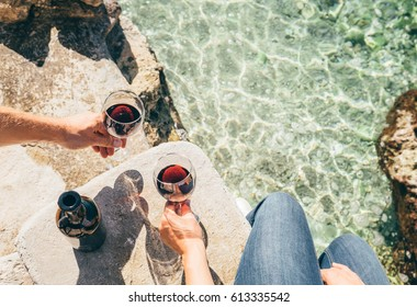 Close up image man and woman hands with goblet of wine at the sea side