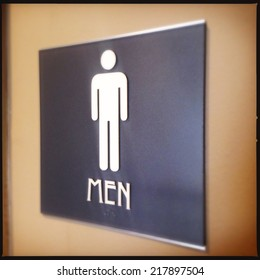 Close up image of a men's room sign