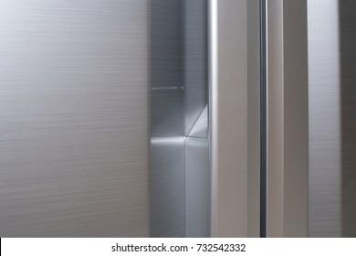 CLOSE UP IMAGE OF METALLIC STAINLESS STEEL MODERN FRIDGE DOOR HANDLES