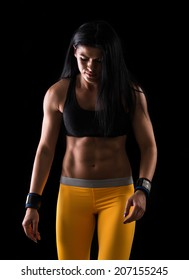 Close up image of middle eastern female in sports clothing relaxing after workout on black background. Muscular female body with sweat