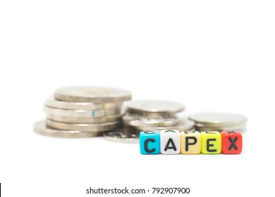 Close up image of the multicolor alphabet dices which are arranged for a word CAPEX in front of stack of coins, isolated on white background.