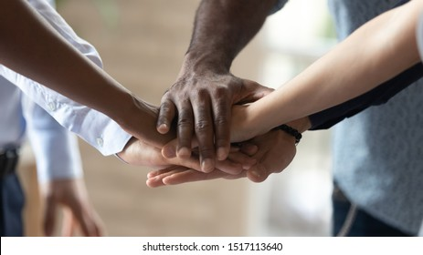 Close up image multiracial people standing in circle, joining hands in middle, showing support, demonstrating mixed race team unity. Group of diverse people involved in team building activity.
