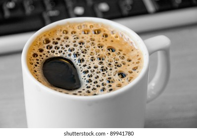 close up image of a newly brewed cup of foamy coffee in front of a computer keyboard