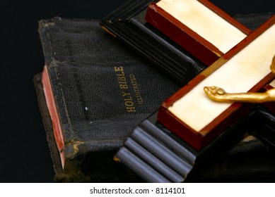 close up image of an old crucifix laying on top of an ancient leatherbound bible