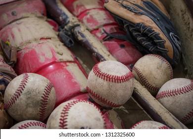 A close up image of an old used baseball, baseball bat, and baseball glove