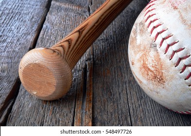 A close up image of an old used wooden baseball bat and baseball glove.