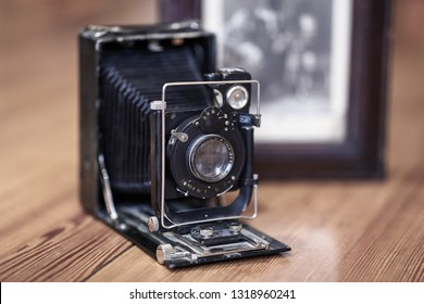 Close up image of old vintage dusty camera with old picture on blurred background, selective focus. Wooden table, indoors, retro effect, copy space.