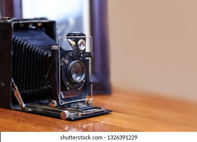 Close up image of old vintage dusty camera with old picture on blurred background, selective focus. Wooden table, indoors, retro effect, copy space, place for any text.